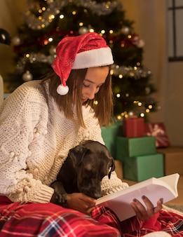 Frau, die weihnachtsmütze an weihnachten trägt und buch mit ihrem hund liest