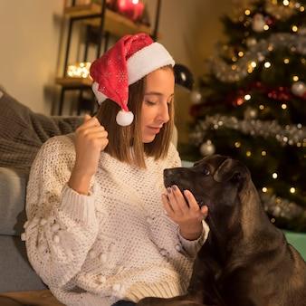 Frau, die weihnachtsmütze an weihnachten und ihrem hund trägt