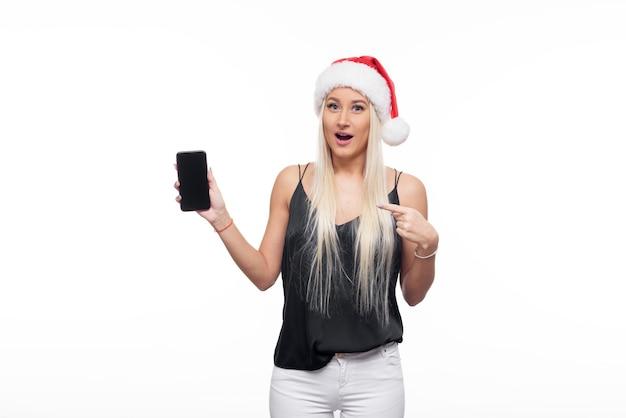 Frau, die weihnachtsmütze mit handy trägt