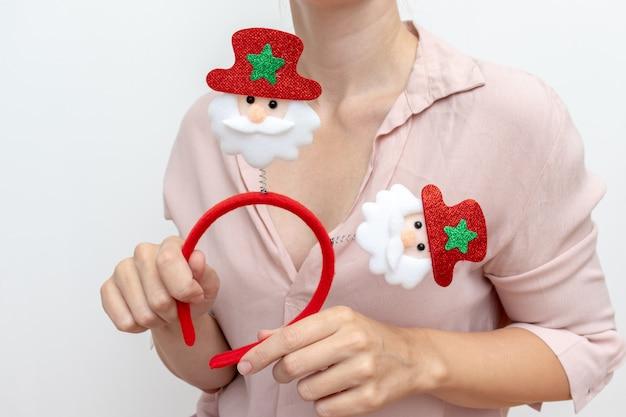 Frau, die weihnachtszubehör mit weihnachtsmännern hält