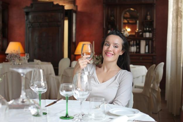 Frau, die weine in einem restaurant schmeckt