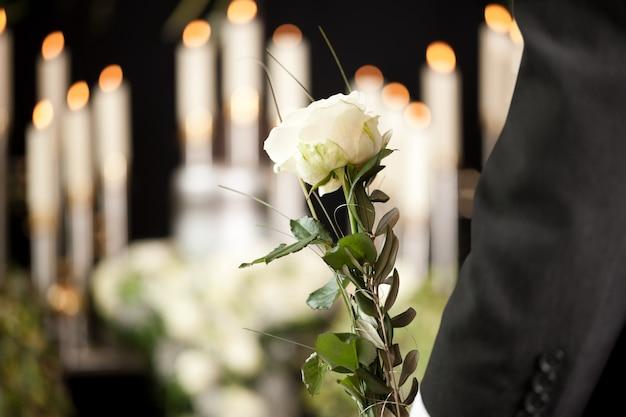 Frau, die weiße blume im begräbnis hält