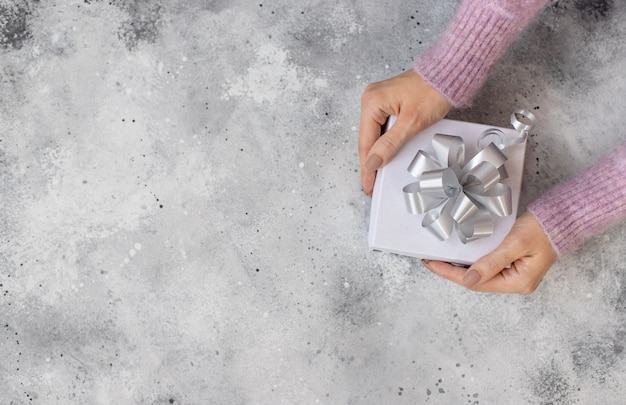 Frau, die weiße geschenkbox mit silbernem bogen gibt