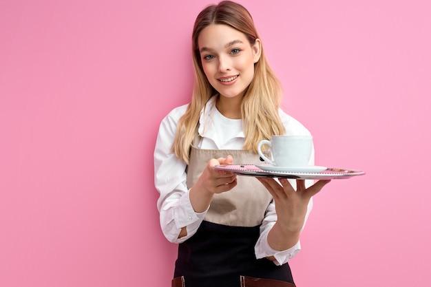 Frau, die weiße klassische tasse für kaffee oder tee auf tablett lokalisiert über rosa studiohintergrund hält.