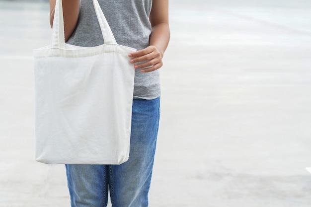 Frau, die weiße leere einkaufstasche hält