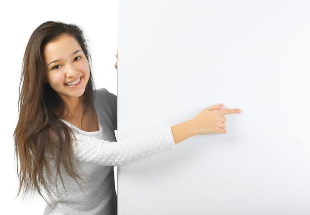Frau, die weiße leere zeichenanschlagtafel zeigend lächelt