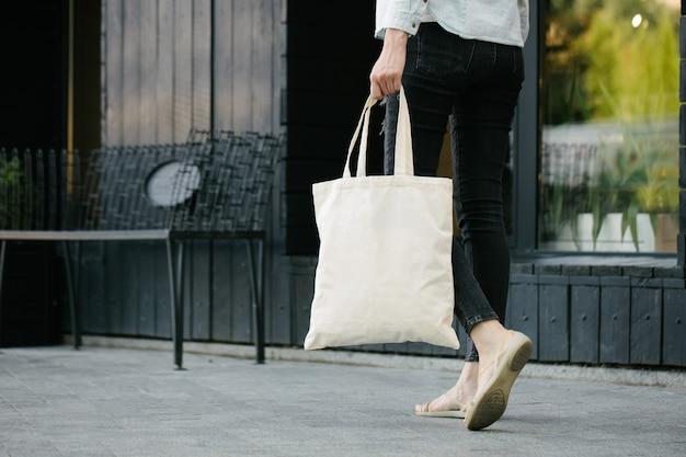 Frau, die weiße textilöko-tasche gegen städtischen stadthintergrund hält. . ökologie- oder umweltschutzkonzept. weiße öko-tasche zum mock-up.