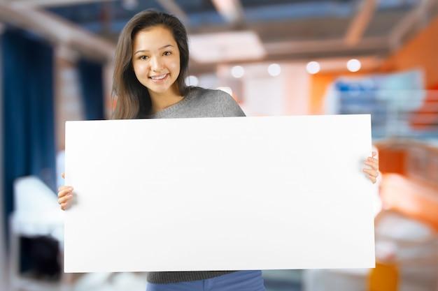 Frau, die weiße unbelegte zeichenanschlagtafel zeigend lächelt