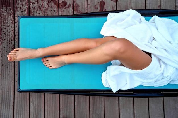 Frau, die weißen bademantel mit schönen glatten schlanken langen beinen trägt, die auf einer liege am kurort liegen