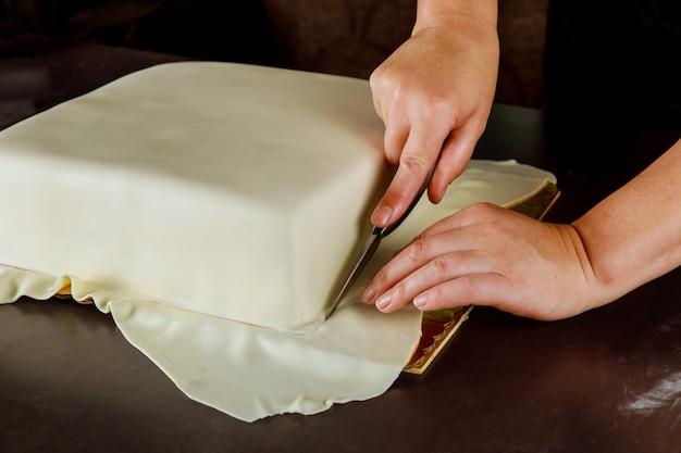 Frau, die weißen fondant auf quadratischem kuchen schneidet. technik der herstellung von hochzeitstorte.