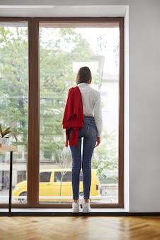 Frau, die weißes hemd und blaue jeans trägt, die nahe dem fenster stehen