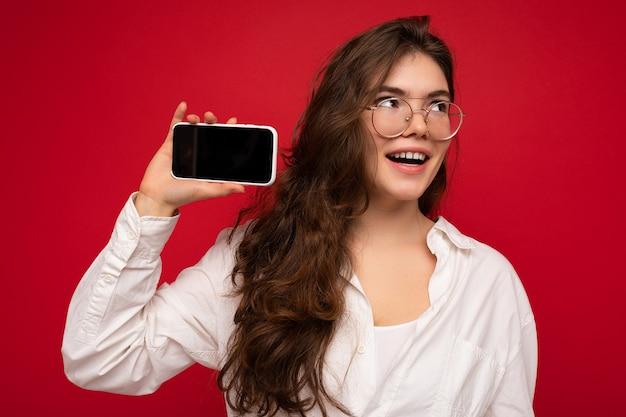 Frau, die weißes hemd und optische brille trägt, lokalisiert über rote wand, die in der hand hält und handy mit leerem bildschirm zeigt