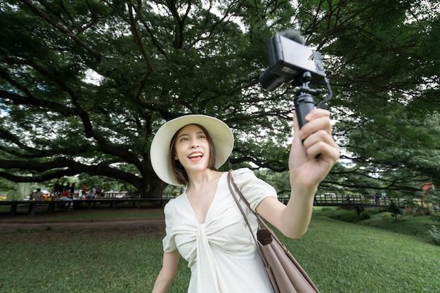 Frau, die weißes kleid trägt, das selfie unter den riesenaffen-pod-bäumen in kanchanaburi, thailand nimmt.