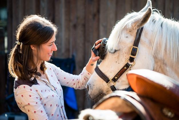 Frau, die weißes pferd schrubbt