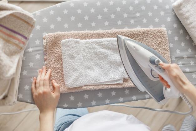 Frau, die weißes tuch bügelt, draufsicht.