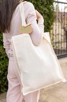 Frau, die wiederverwendbare tasche mit umweltzeichen hält