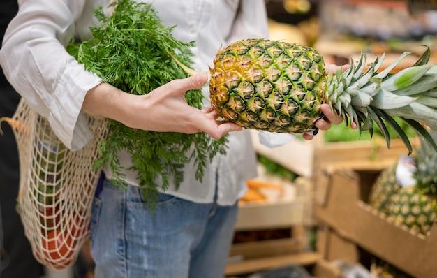 Frau, die wiederverwendbare tasche und ananas im lebensmittelgeschäft hält