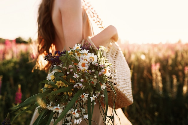 Frau, die wildflowersblumenstrauß im strohbeutel, gehend in blumenfeld auf sonnenuntergang hält.