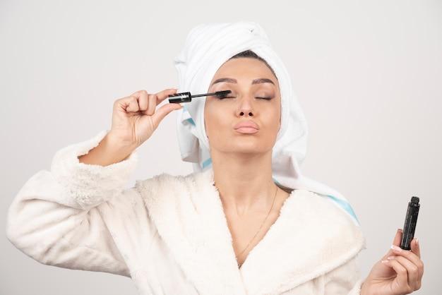 Frau, die wimperntusche im handtuch und im bademantel anwendet.