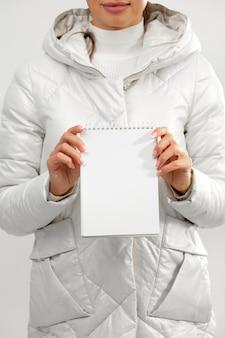 Frau, die winterkleidung hält, die notizbuch hält