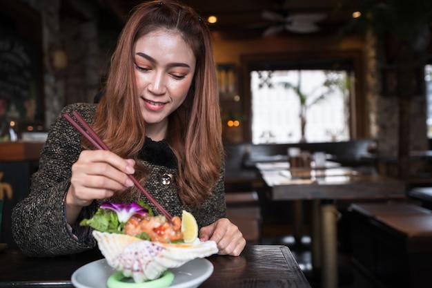 Frau, die würzigen salat des lachssashimis im restaurant isst