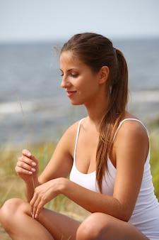 Frau, die yoga am strand macht