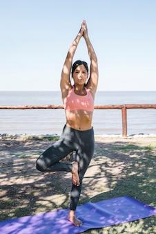 Frau, die yoga am strand tut
