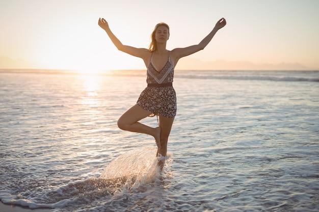 Frau, die yoga am strand während der dämmerung tut