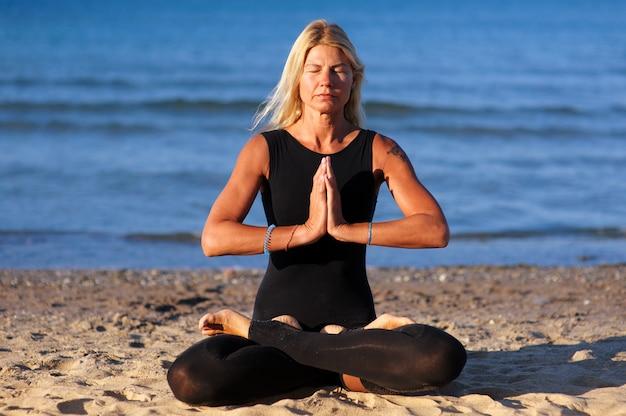 Frau, die yoga asana am strand tut