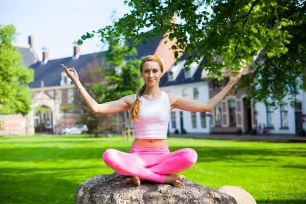 Frau, die yoga asana trainer im park meditiert und tut