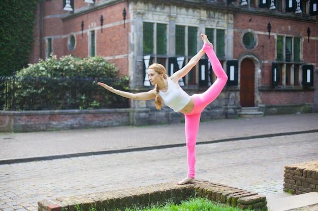 Frau, die yoga asana trainer in der stadtstraße meditiert und tut
