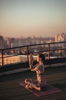 Frau, die yoga auf dem dach eines wolkenkratzers in der großstadt tut