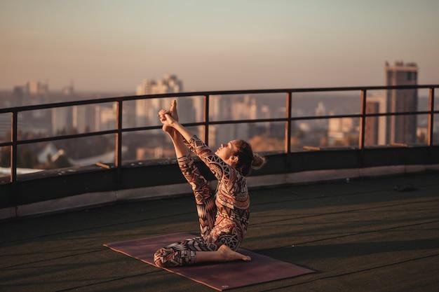 Frau, die yoga auf dem dach eines wolkenkratzers in der großstadt tut.