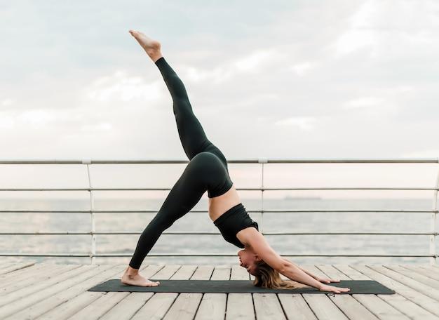 Frau, die yoga auf dem strand in schwieriger asana position tut