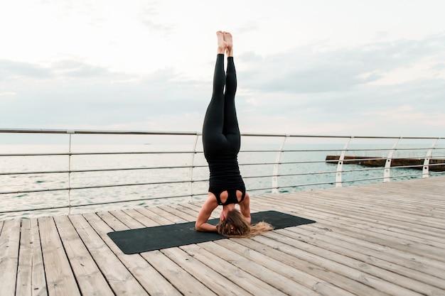 Frau, die yoga auf dem strand tut und auf ihren händen steht