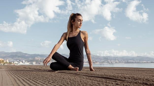 Frau, die yoga auf dem strandsand praktiziert