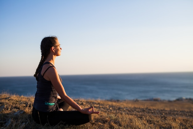 Frau, die yoga auf der natur im freien tut