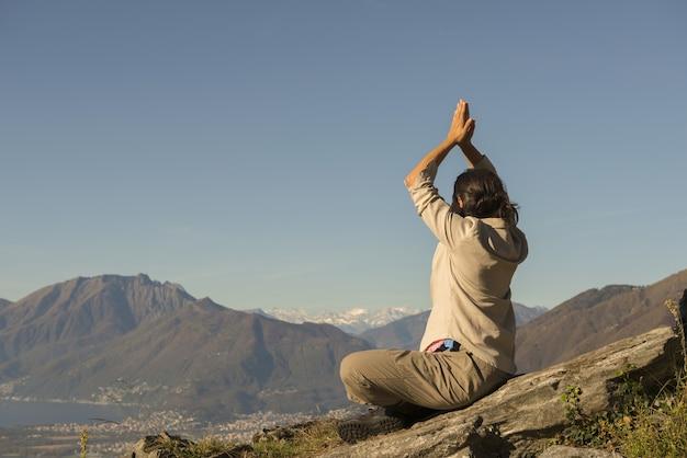 Frau, die yoga auf der spitze eines berges an einem sonnigen tag in der schweiz tut
