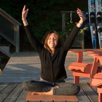 Frau, die yoga auf einer plattform im freien, see des holzes, ontario, kanada tut