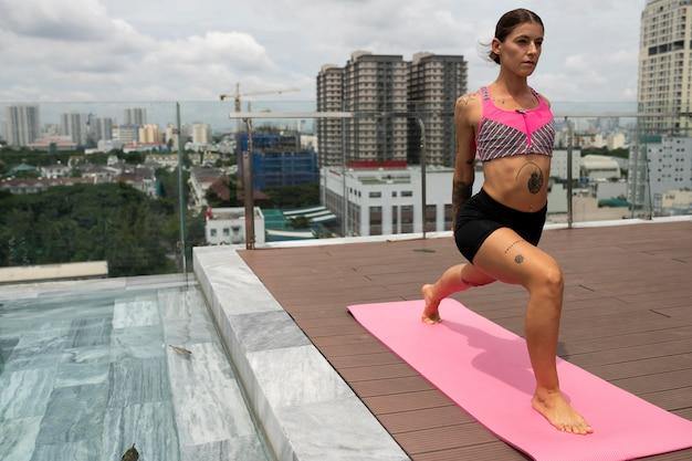 Frau, die yoga auf matte neben pool im freien praktiziert