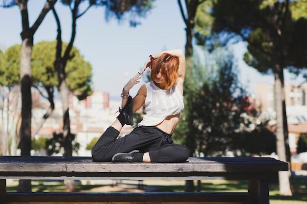 Frau, die yoga auf parkbank tut