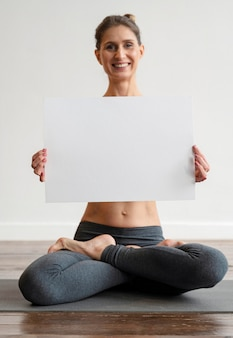 Frau, die yoga ausübt und leeres plakat hält