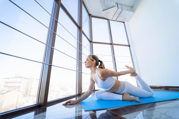Frau, die yoga beim sitzen in der taubenhaltung tut