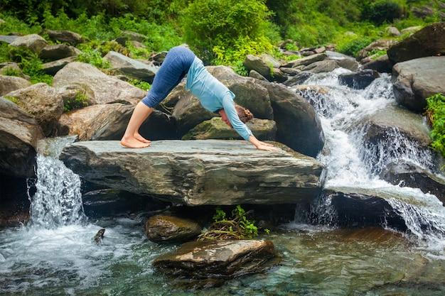 Frau, die yoga draußen am tropischen wasserfall tut
