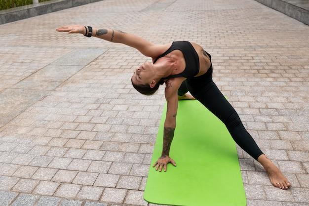 Frau, die yoga draußen auf matte tut