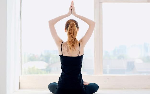 Frau, die yoga drinnen in der nähe des fensters macht und mit ihren händen zurückansicht gestikuliert.