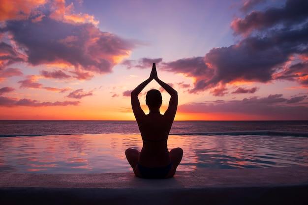 Frau, die yoga gegen die untergehende sonne tut.