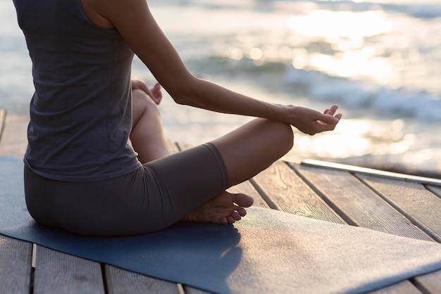 Frau, die yoga gegenüber meer tut