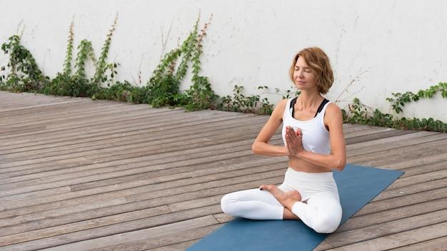 Frau, die yoga-haltung auf matte außerhalb praktiziert