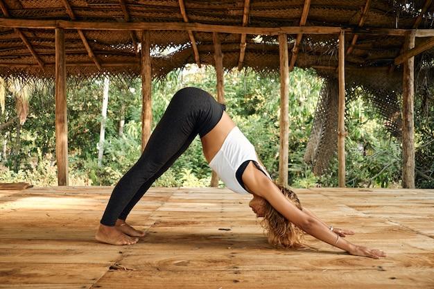 Frau, die yoga im tropischen offenen yoga-studio-platz praktiziert